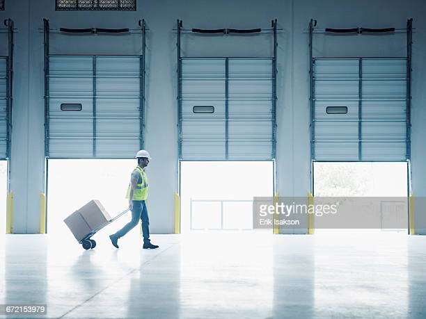 indian worker pulling hand truck near open loading dock doors - loading dock stock pictures, royalty-free photos & images