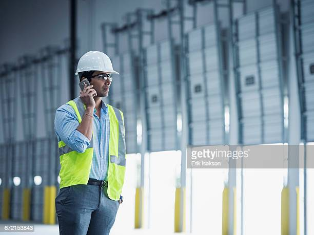 Indian worker talking on cell phone at loading dock