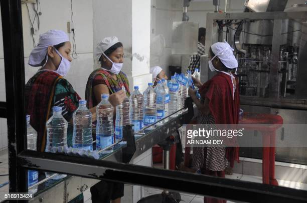 Indian workers add labels onto bottles of drinking water at a bottling unit on World Water Day in Agartala capital of northeastern state of Tripura...