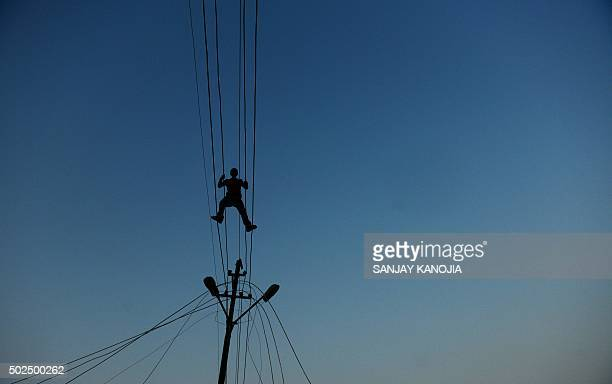 TOPSHOT Indian workers adjust electricity cables set up temporarily on the banks of the river Ganga in preparation for the annual Hindu religious...