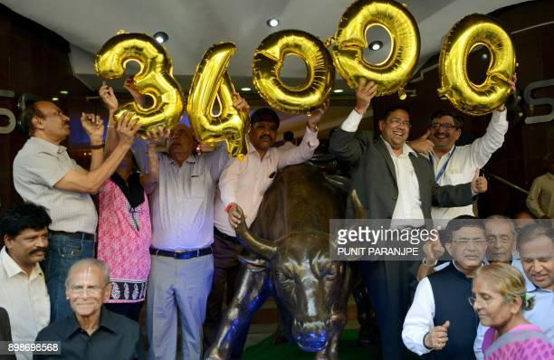 Indian workers and brokers gather outside the Bombay Stock Exchange to celebrate the benchmark 30share index SENSEX crossing 34000 points in Mumbai...