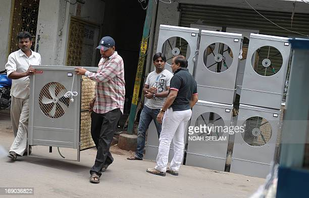 Indian workers carry an air cooler outside a shop in Hyderabad on May 19 2013 Air coolers are in high demand during the summer months as temperatures...