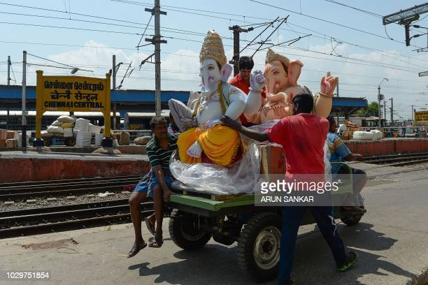 Indian workers carry an idol of the elephantheaded Hindu deity Lord Ganesh at a railway station in Chennai on September 9 ahead of the upcoming...