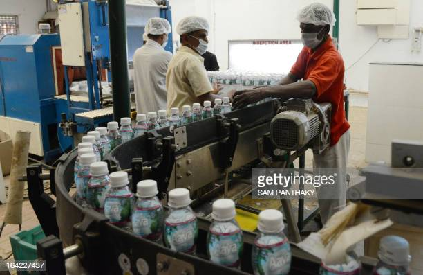 Indian workers check bottles at an automated refilling production line at the Aava natural mineral water plant in Ahmedabad on March 21 on the eve of...