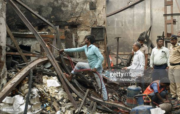 Indian workers clear metal debris from the scene of a fire in Mumbai on December 18 2017 Fire tore through a sweet shop in the Indian city of Mumbai...