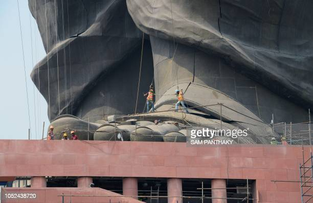TOPSHOT Indian workers give the finishing touches to the world's tallest statue dedicated to Indian independence leader Sardar Vallabhbhai Patel...