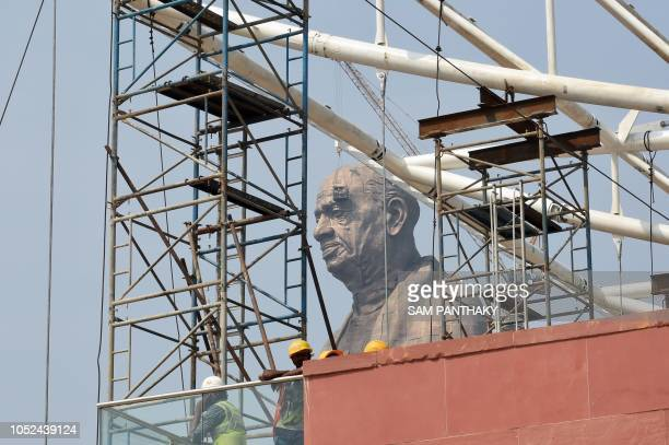 Indian workers give the finishing touches to the world's tallest statue dedicated to Indian independence leader Sardar Vallabhbhai Patel overlooking...