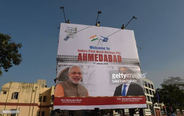 Indian workers hang a billboard bearing images of Israeli Prime Minister Benjamin Netanyahu and Indian Prime Minister Narendra Modi in Ahmedabad on...