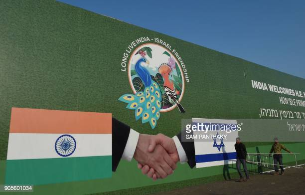 Indian workers hang a billboard bearing the national flags of Israel and India in Ahmedabad on January 16 2018 Israeli Prime Minister Benjamin...