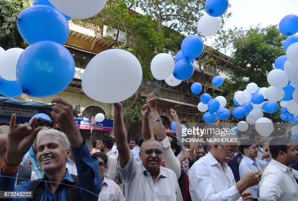 Indian workers holding balloons gather outside the Bombay Stock Exchange to celebrate the benchmark 30 share index SENSEX crossing 30000 points in...