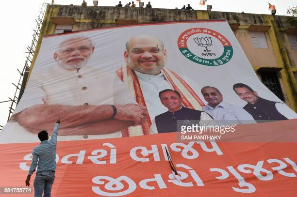 Indian workers install a huge poster with Indian Prime Minister Narendra Modi Bhartiya Janta Party Chief Amit Shah Gujarat state Chief Minister...