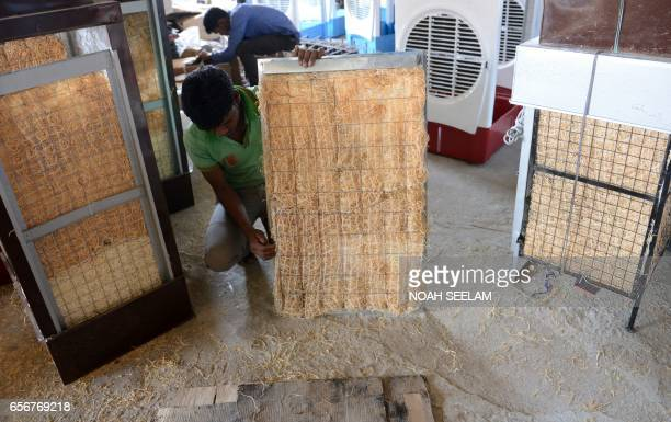 Indian workers make air coolers with frames and pads of shredded wood fibre at a factory in Hyderabad on March 23 2017 Air coolers with their...