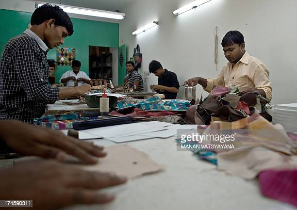 Indian workers make recycled goods at a workshop run by Green The Gap store in New Delhi on July 26, 2013. Green the Gap, an Indian recycling company...