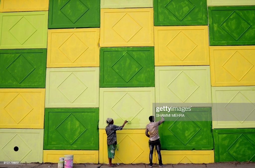 TOPSHOT Indian workers paint the wall of a flyover on a road in Jalandhar on January 25 2018 / AFP PHOTO / Shammi MEHRA