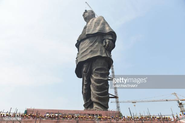 TOPSHOT Indian workers pose at the base of the world's tallest statue dedicated to Indian independence leader Sardar Vallabhbhai Patel overlooking...