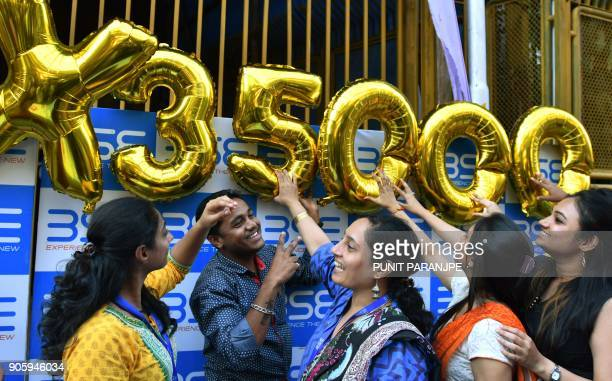 Indian workers pose outside the Bombay Stock Exchange during celebrations marking the benchmark 30share index SENSEX crossing 35000 points in Mumbai...