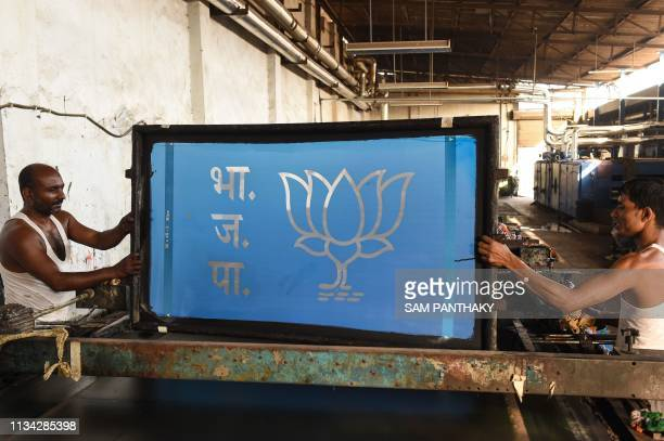 Indian workers prepare a frame for the textile materials dedicated to the Bhartiya Janta Party ahead of India's general election on the outskirts of...