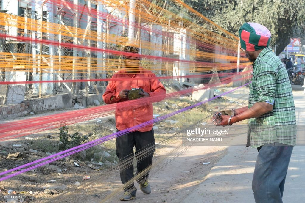 Indian workers prepare balls of coloured kite thread at the roadside ahead of the forthcoming Lohri Festival in Amritsar on January 7 2018 The Lohri..