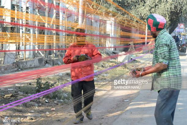 Indian workers prepare balls of coloured kite thread at the roadside ahead of the forthcoming Lohri Festival in Amritsar on January 7 2018 The Lohri...