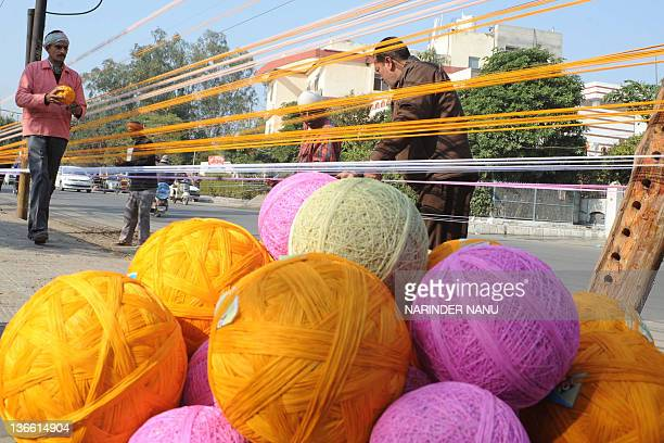 Indian workers prepare balls of coloured kite thread by a roadside in Amritsar on January 9 2012 ahead of the Lohri Festival The Lohri harvest...