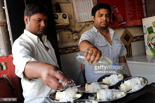 Indian workers prepare dishes of Matka Kulfi at The Mahajan Refreshment House in Amritsar on April 29, 2010. At the sixty year old establishment in...