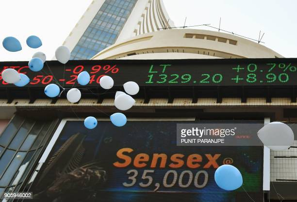 Indian workers release balloons outside the Bombay Stock Exchange to celebrate the benchmark 30share index SENSEX crossing 35000 points in Mumbai on...