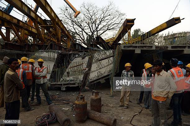 Indian workers stand at the site of an underconstruction bridge collapse at the international airport in Mumbai on February 7 2013 The collapse of a...