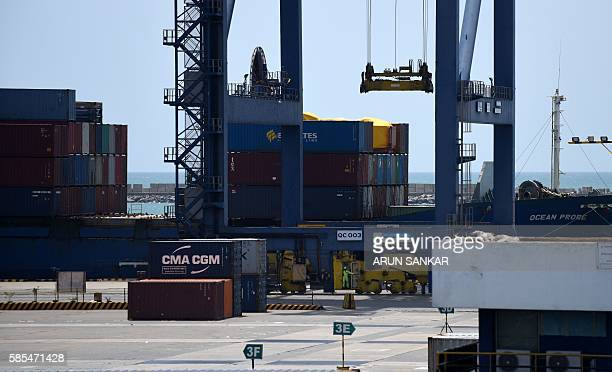 Indian workers use a crane to move crates at a container terminal in Chennai harbour on August 3 2016 Finance Minister Arun Jaitley said India was on...