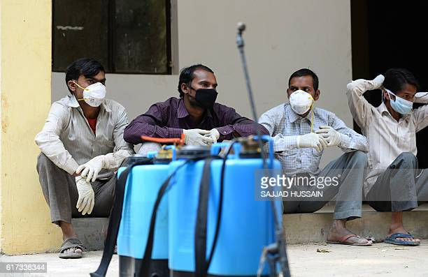 Indian workers wearing protective masks sit inside the Deer Park which is temporarily closed for visitors as a precautionary measure amidst a bird...