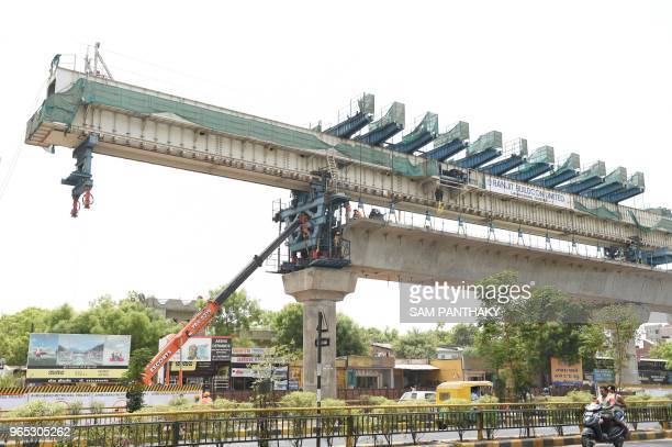 Indian workers work on the under construction Ahmedabad Metro Rail project in Ahmedabad on June 1 2018 The MetroLink Express project will be...