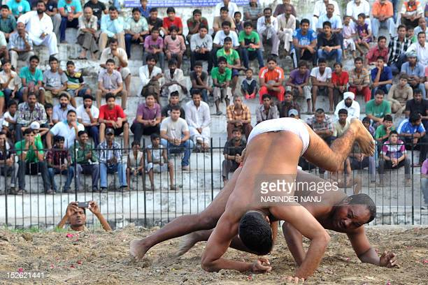 Indian wrestlers or 'Pahalwan' Aman and Jamun wrestle during a Kushti competition at Gol Bagh Wrestling Stadium in Amritsar on September 23 2012...