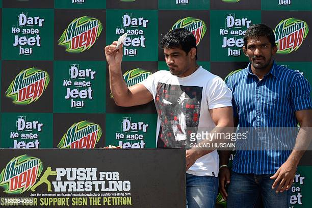 Indian wrestlers Sushil Kumar and Yogeshwar Dutt drop a petition letter into a collection box during a promotional campaign in New Delhi on March 7...