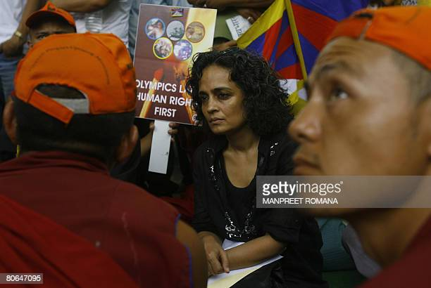 Indian writer Arundhati Roy chats with Tibetan monks during a protest in New Delhi on April 12 2008 Several thousand Tibetans marched in the Indian...