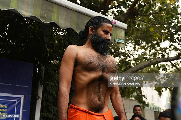 Indian yoga guru Baba Ramdev demonstrates a yoga exercise to the media during a press conference on the declaration of a 'yoga day' in New Delhi on...