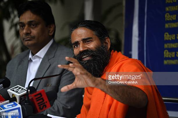 Indian yoga guru Baba Ramdev gestures as he speaks to the media during a press conference on the decleration of a 'yoga day' in New Delhi on December...