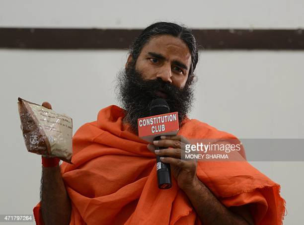 Indian yoga guru Baba Ramdev poses with an ayurvedic health product during a press conference in New Delhi on May 1 2015 A hugely popular Indian guru...