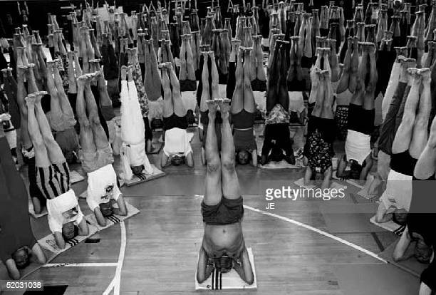 Indian yoga master BKS Iyengqr stands on his head 24 August 1993 along with his followers at an international yoga convention at Crystal Palace