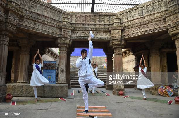 Indian yoga practitioners take part in a yoga session on International Yoga Day at the 15th century Adalaj Stepwell in Adalaj some 40km from...