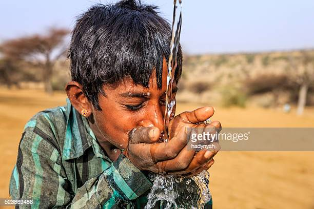 Indian young boy drinking fresh water, desert village, Rajasthan, India