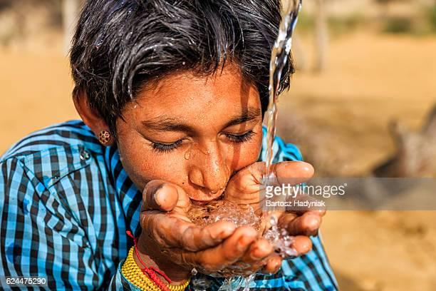 Indischer junge trinkt Wasser, desert village, Rajasthan, Indien