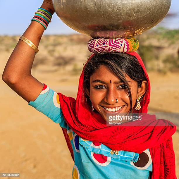 Indian young girl carrying on her head water from well