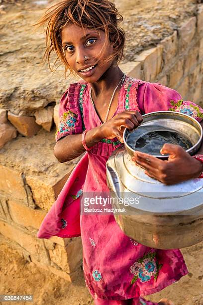 Indian young girl carrying water from a well, Rajasthan