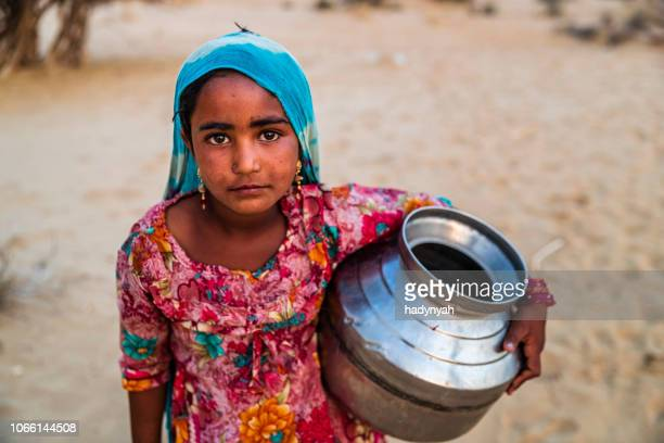 indian young girl carrying water from well, desert village, india - child labour stock pictures, royalty-free photos & images