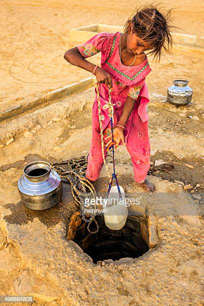 indian young girl drawing water from a well, rajasthan - human arm stockfoto's en -beelden