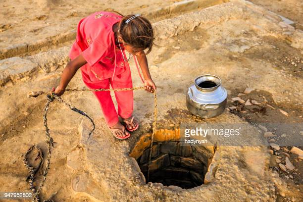 indian young girl drawing water from a well, rajasthan - drought stock pictures, royalty-free photos & images