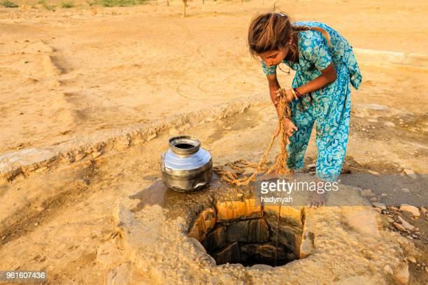 indiase meisje tekening water uit een put, rajasthan - putten stockfoto's en -beelden