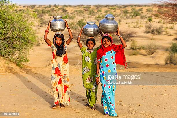 Indian young girls carrying on their heads water from well