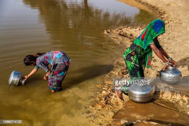 indische meisjes verzamelen van drinkbaar water uit het meer, woestijn dorp, india - human arm stockfoto's en -beelden
