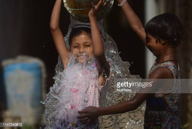 Indian young girls take bath from a municipal water pump to cool off themmselves during a scorching hot day in Allahabad on June 1 2019 Two thirds of...