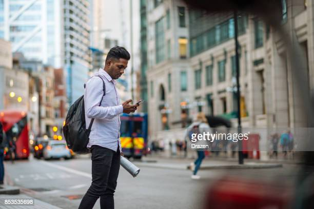 indian young man in london, crossing the busy street while multi tasking - crossroad stock pictures, royalty-free photos & images